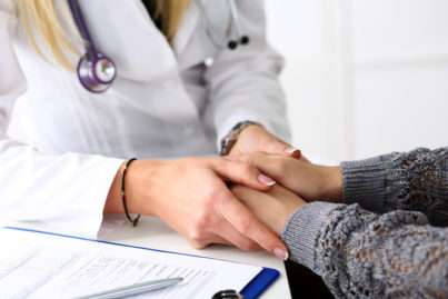 Friendly female doctor hold patient hand in office during reception. Examination result, positive test, calm down, promise and cheer up, grief and suffer, treatment, condolence, ethics concept